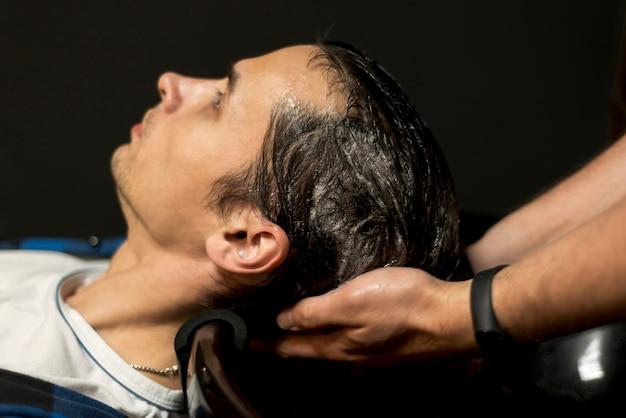 Schließen sie herauf den mann, der sein haar gewaschen erhält Kostenlose Fotos