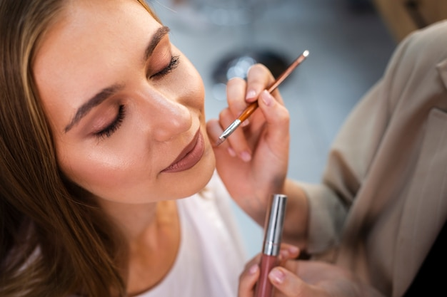 Schließen sie herauf den maskenbildner, der nackten lippenstift auf frau mit bürste anwendet Kostenlose Fotos