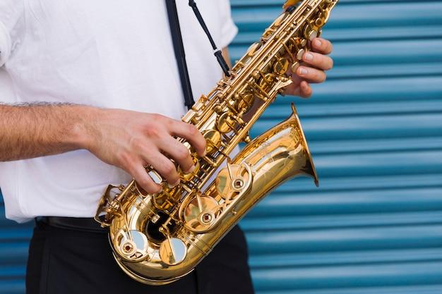 Schließen sie herauf den musiker, der saxophon hält Kostenlose Fotos