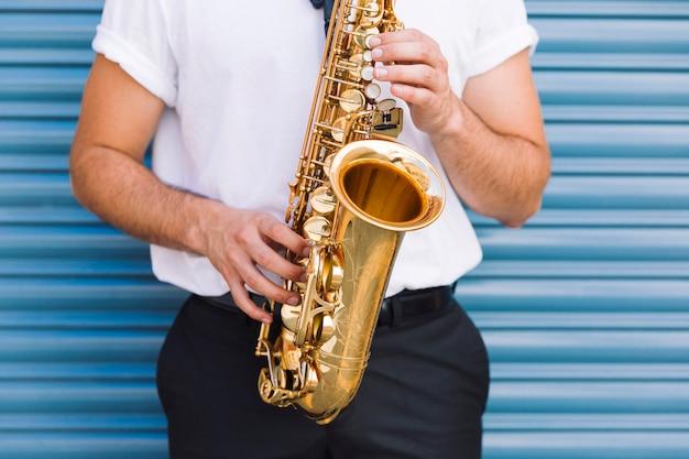 Schließen sie herauf den musiker, der saxophon spielt Kostenlose Fotos