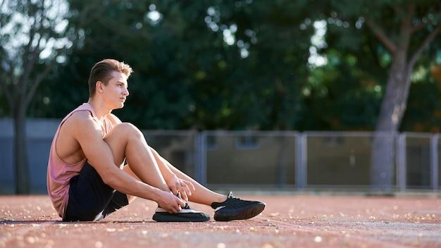 Schließen sie herauf den schuss des jungen mannes des athletenläufers, der sein bein auf rennstrecke im stadion ausdehnt und für das ausarbeiten sich vorbereiten. kaukasischer mann, der draußen tragende blaue sportkleidung trainiert. sport, leute, lebensstil Premium Fotos