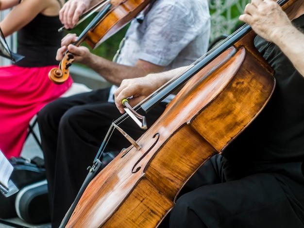 Schließen sie herauf den straßenmusiker, der violineninstrument-jazzmusikausführenden spielt Premium Fotos