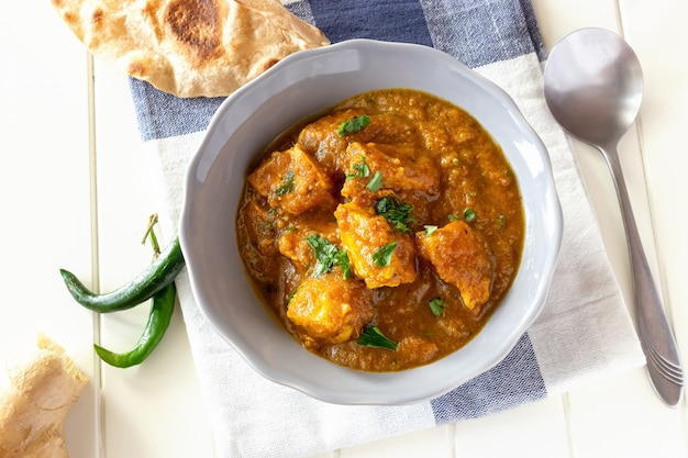 Schließen sie herauf den traditionellen indischen butterhuhncurry, der mit chapati-brot in der schüssel gedient wird. ansicht von oben. Premium Fotos