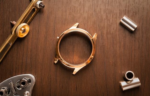 Schließen sie herauf des glänzenden goldenen edelstahl-uhrengehäuses, das auf reparatur wartet, weinleseholz-uhrmachertisch mit werkzeug und ausrüstung für service-hintergrundkonzept Premium Fotos