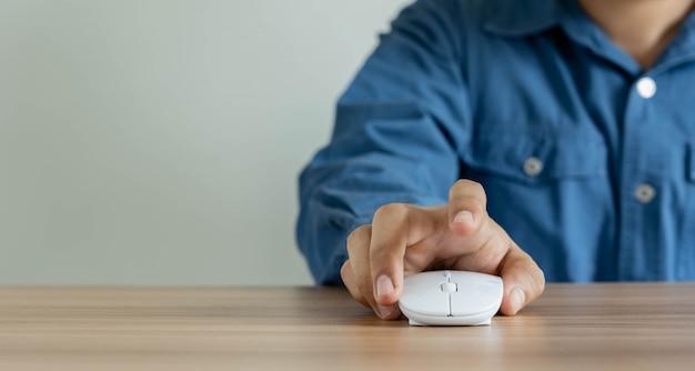 Schließen sie herauf des jungen mannes, der eine maus des computers auf dem schreibtisch verwendet Premium Fotos