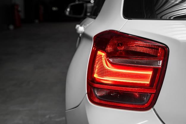 Schließen sie herauf detail über eines des modernen weißen limousinenautos des roten rücklichts led. außendetail automobil. Premium Fotos