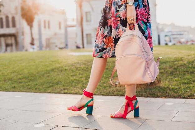 Schließen sie herauf details der beine in den rosa sandalen der stilvollen frau, die in der stadtstraße in bedrucktem buntem rock geht und rosa lederrucksack hält, sommerart-schuhtrend Kostenlose Fotos