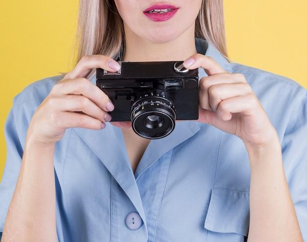 Schließen sie herauf die frau, die eine kamera hält Kostenlose Fotos