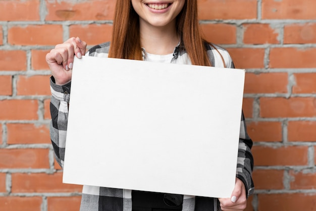 Schließen sie herauf die frau, die leeres papier zeigt Kostenlose Fotos