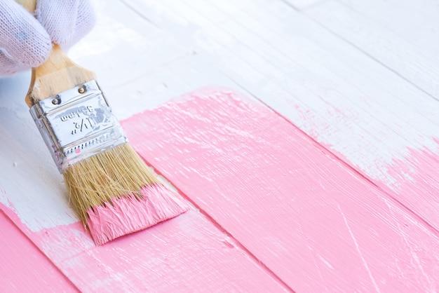 Schließen sie herauf die frauenhand, die bürste hält, die rosa farbe auf einem weißen holztisch malt. Premium Fotos