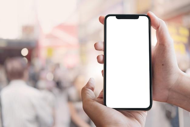 Schließen sie herauf die frauenhand, die ein intelligentes telefon mit leerem bildschirm am maket verwendet. Premium Fotos