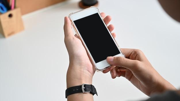 Schließen sie herauf die frauenhand, die ein intelligentes telefon mit leerem bildschirm am schreibtisch verwendet. Premium Fotos