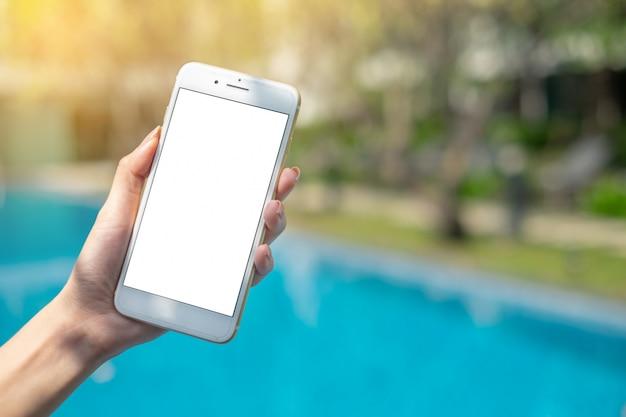 Schließen sie herauf die frauenhand, die weißes telefon auf leerem bildschirm am beschneidungspfad insi des parks im freien hält Premium Fotos