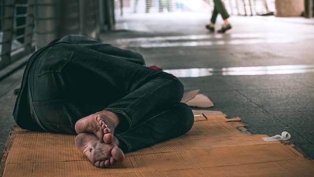 Schließen sie herauf die füße des obdachlosen mannes, der auf dem schmutzigen boden auf der städtischen straße in der stadt schläft Premium Fotos