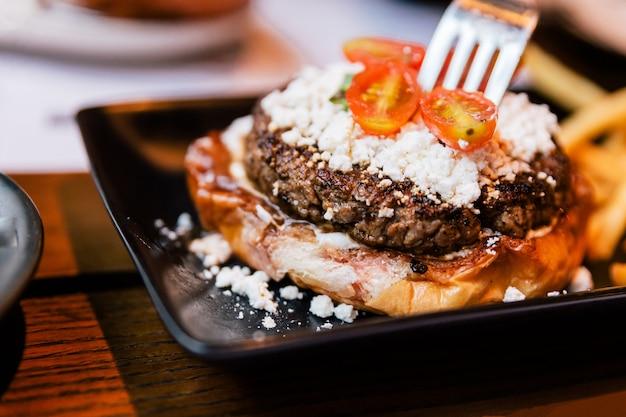 Schließen sie herauf die gabel, die cheeseburger mit gegrilltem rindfleisch sticht Premium Fotos