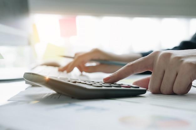 Schließen sie herauf die geschäftsfrau, die taschenrechner und laptop für verwendet, mathefinanzierung auf hölzernem schreibtisch im büro- und geschäftsarbeitshintergrund Premium Fotos