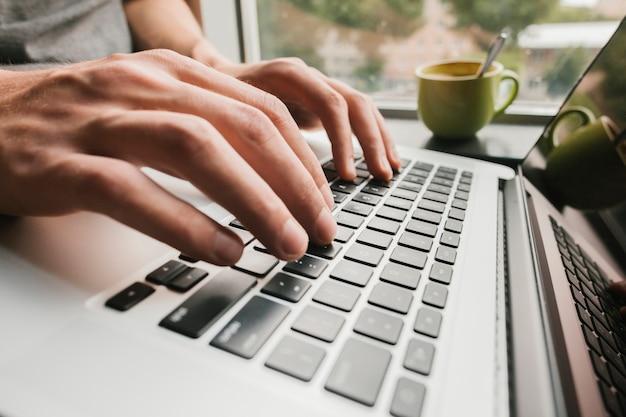 Schließen sie herauf die hände, die auf laptop schreiben Kostenlose Fotos