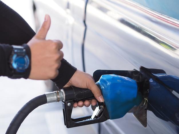 Schließen sie herauf die hand des mannes benzinkraftstoff im auto an der tankstelle pumpend. Premium Fotos