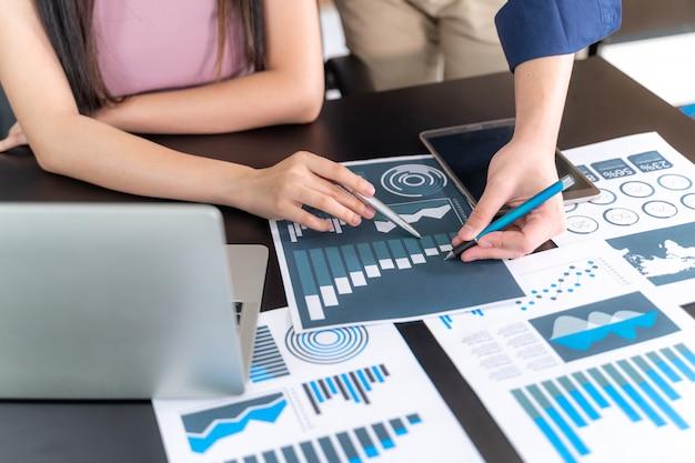 Schließen sie herauf die hand des marketing-manager-angestellten zeigend auf geschäftsdokument während der diskussion am konferenzzimmer, notizbuch auf hölzerner tabelle - geschäftskonzept Kostenlose Fotos