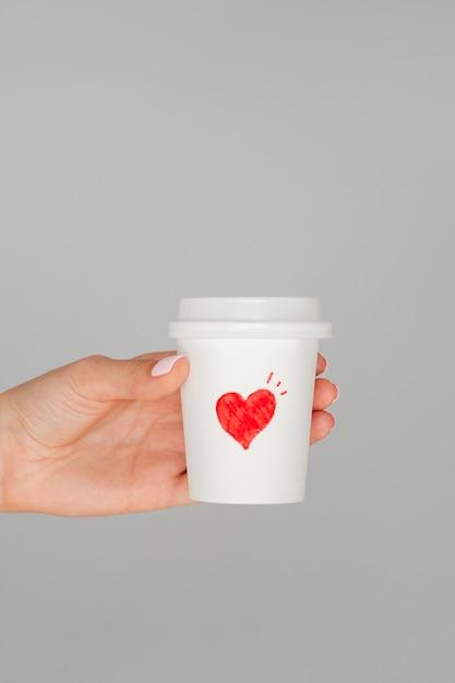Schließen sie herauf die hand, die valentinsgrußkaffee hält Kostenlose Fotos
