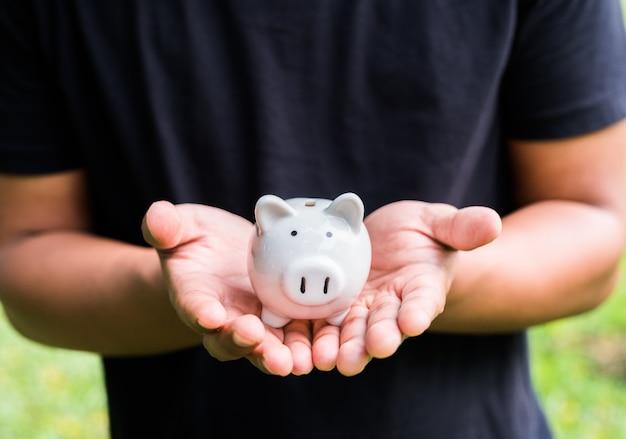 Schließen sie herauf die männlichen hände, die sparschwein halten. Premium Fotos