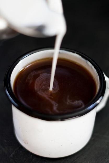 Schließen sie herauf die milch, die in schwarzen kaffee gegossen wird Kostenlose Fotos