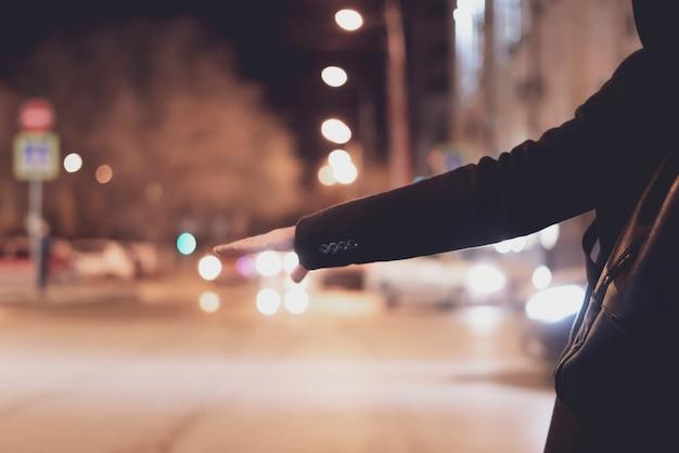 Schließen sie herauf die personenhand, die per anhalter fährt und auf einen autostand auf einer landstraße in der nacht wartet Premium Fotos