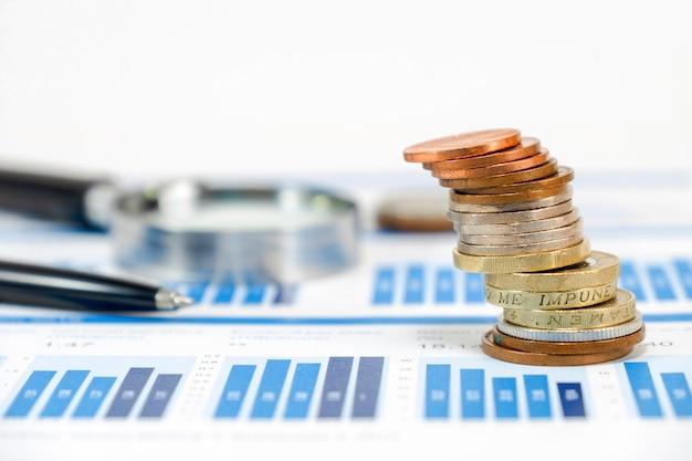 Schließen sie herauf die sterlingmünzen, die auf kapitaldiagramm mit stift- und vergrößerungsglasglas stapeln Premium Fotos