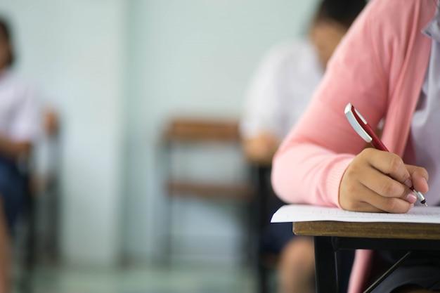 Schließen sie herauf die studenten, die prüfungsantwortblattübungen im klassenzimmer der schule mit druck schreiben und lesen. Premium Fotos