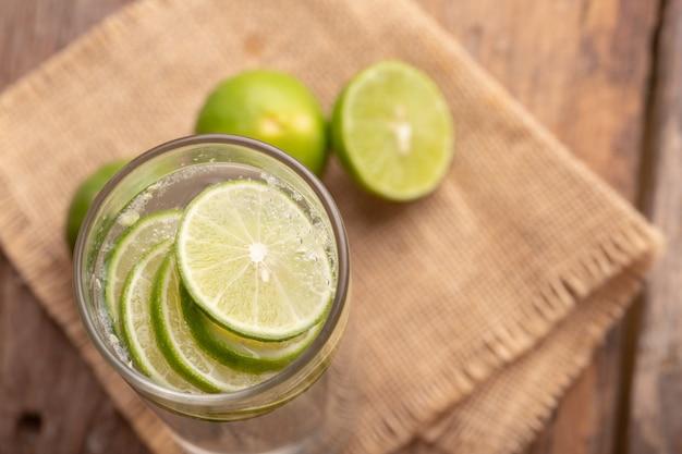 Schließen sie herauf die zitrone, die im glas mit sodawasser und der hälfte des grünen kalkplatzes auf gesponnenem sack und holztisch geschnitten wird Premium Fotos