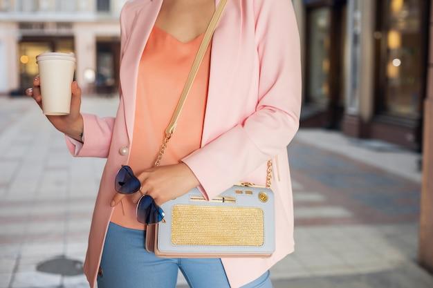 Schließen sie herauf einzelheiten der accessoires der frau in der stilvollen kleidung, die in der straße geht, die sonnenbrille, handtasche, gekleidet in rosa jacke, kaffeetrinken, frühlingssommer-modetrend hält Kostenlose Fotos