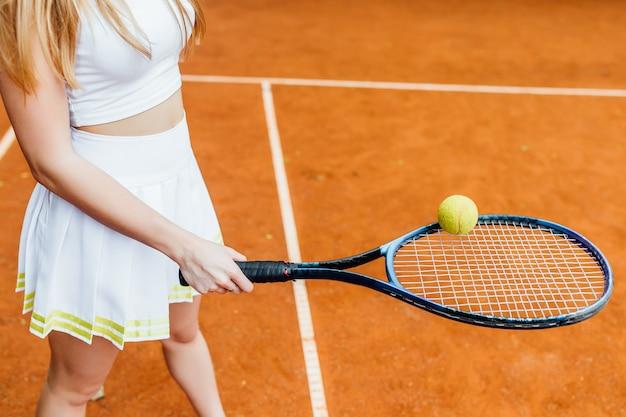 Schließen sie herauf foto, das mädchen, das tennis auf dem gericht spielt. Premium Fotos