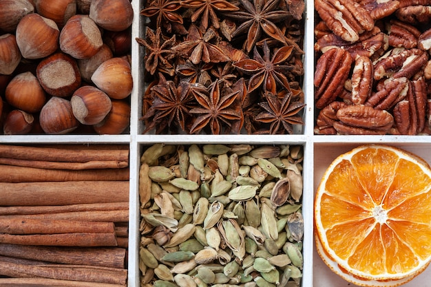 Schließen sie herauf foto von zimtrinden, von haselnüssen, von anis, von pekannüssen, von scheiben der trockenen orange und von kardamom. Premium Fotos