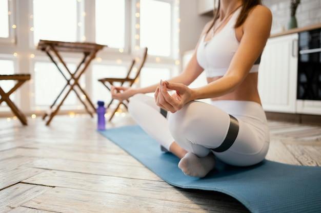 Schließen sie herauf frau, die zu hause meditiert Kostenlose Fotos