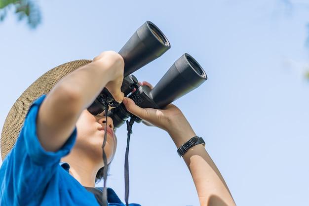 Schließen sie herauf frauenabnutzungshut und halten sie binokulares in der rasenfläche Premium Fotos