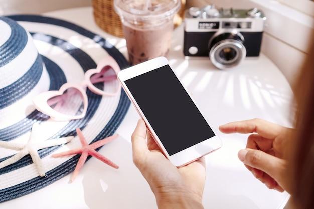 Schließen sie herauf frauenhände unter verwendung des smartphones auf weißem tisch, reisekonzept. flache lage, kopierraum Premium Fotos