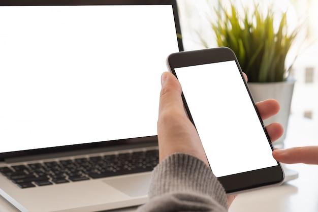 Schließen sie herauf frauenhand unter verwendung eines intelligenten telefons mit leerem bildschirm zu hause. Premium Fotos