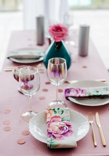 Schließen sie herauf geburtstag oder hochzeit tischdekoration in rosa und farben mit fla napkns, goldenes besteck, rose in vase. babyparty oder mädchenparty. Premium Fotos