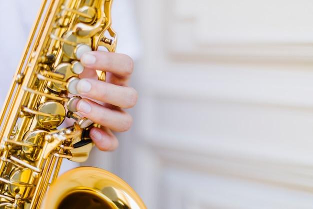Schließen sie herauf gehaltenes saxophon mit unscharfem hintergrund Kostenlose Fotos