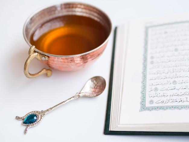 Schließen sie herauf geöffneten quran mit teeschale Kostenlose Fotos