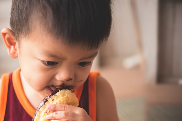 Schließen sie herauf gesicht des hungrigen kleinen jungen eaitng heißen donut Kostenlose Fotos