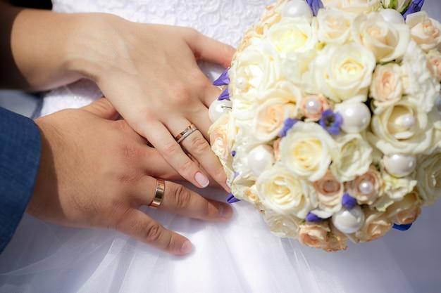 Schließen sie herauf hände der braut und des bräutigams mit hochzeitsblumenstrauß Premium Fotos