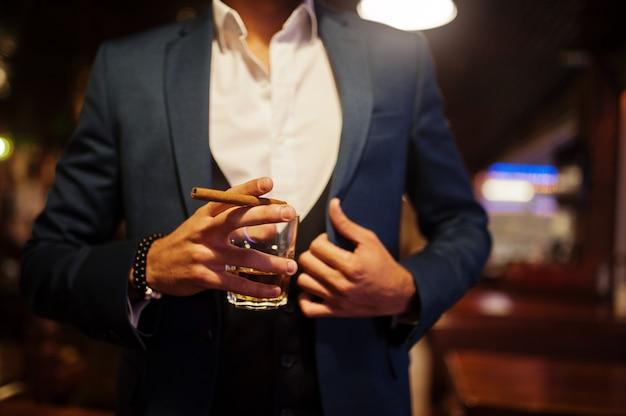 Schließen sie herauf hand des hübschen gut gekleideten arabischen mannes mit dem glas whisky und zigarre, die an der kneipe aufwirft. Premium Fotos