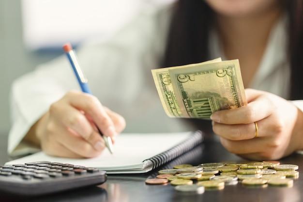 Schließen sie herauf handfrau mit bleistiftschreiben auf dem buch- und handgriff us-dollar. berechnung zu hause Premium Fotos