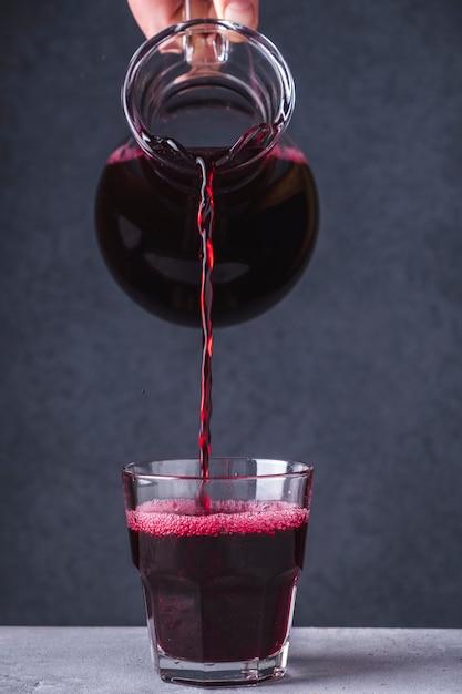 Schließen sie herauf handströmendes fruchtgetränk in einem glas. morse der schwarzen johannisbeere in einem glas. Premium Fotos