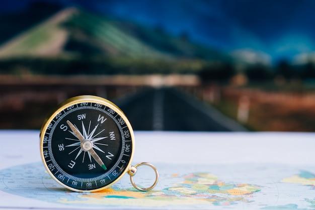 Schließen sie herauf kompass auf papierkarte, reise und lebensstil, handhaben sie zum erfolgsgeschäftstechnologiekonzept. Premium Fotos
