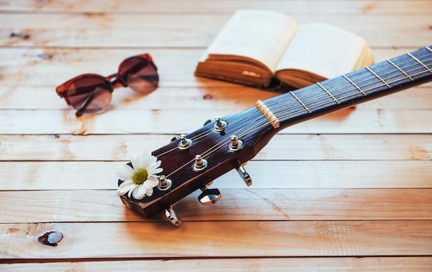 Schließen sie herauf kopf der klassischen gitarre mit gläsern und buch Premium Fotos
