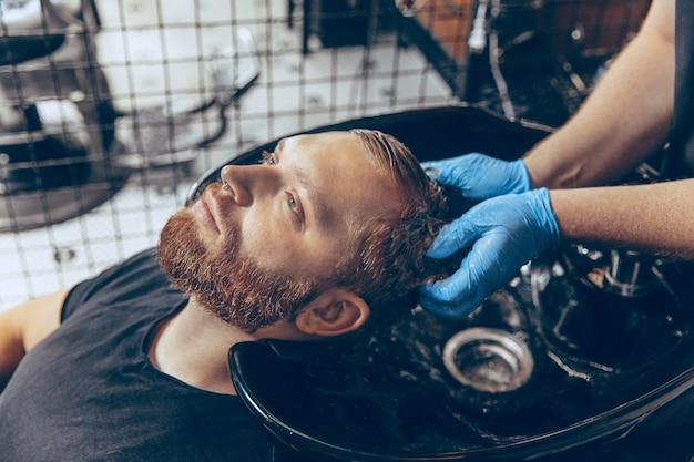 Schließen sie herauf mann, der haarfriseur am friseursalon trägt maske während coronavirus-pandemie schneidet. Kostenlose Fotos