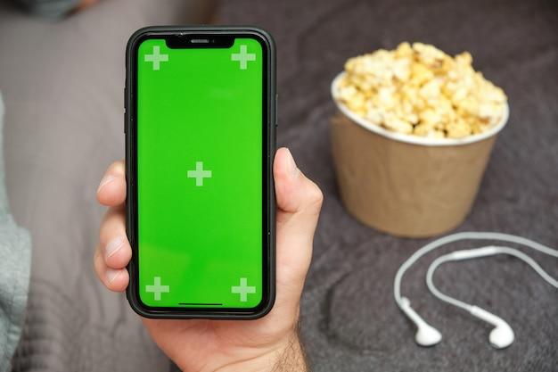 Schließen sie herauf mans hand, die ein mobiltelefon mit xxx-logo hält Premium Fotos