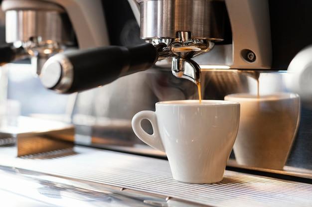 Schließen sie herauf maschine, die kaffee in tasse gießt Kostenlose Fotos